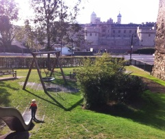 A playground across from the Tower of London. The brick wall on the right is part of the original Roman wall.